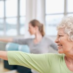 Close-up shot of elderly woman doing stretching workout at yoga class. Women practicing yoga at health club. ** Note: Shallow depth of field